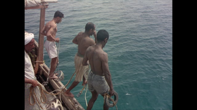 cu man opening oyster and looking for pearls / pearl divers on boat get ready plug their noses and tie ropes around themselves / they jump in the... - golfstaaten stock-videos und b-roll-filmmaterial