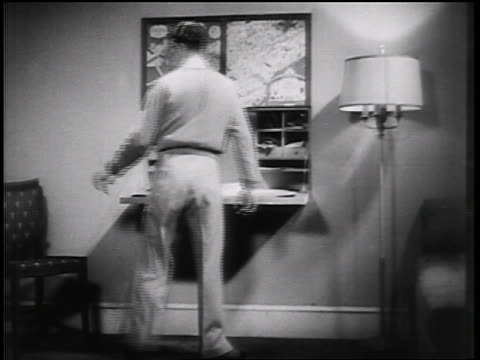 b/w 1935 man opening panels in wall to reveal desk + bookshelves / educational - 1935 stock videos & royalty-free footage