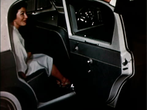 1957 MS Man opening rear door of 1957 Hillman Minx. Stylish, sophisticated woman grabs her gloves and purse and gets out of car / USA