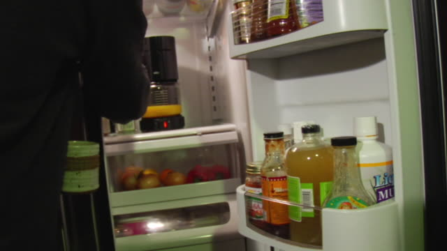 cu man opening refrigerator and pouring orange juice in cup / brooklyn, new york, usa - orangensaft stock-videos und b-roll-filmmaterial
