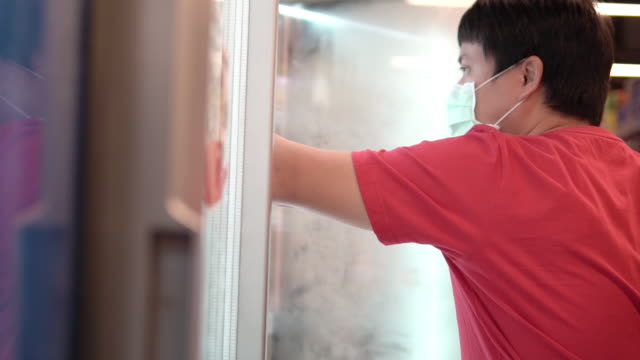 man opening refrigerator in supermarket with bare hand. - part of stock videos & royalty-free footage