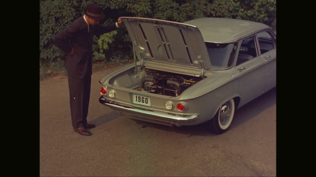 vidéos et rushes de ms zi man opening trunk of car to look at his engine in 1960 chevrolet corvair car / united states - panne de voiture