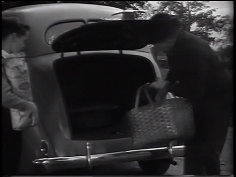 b/w 1937 man opening trunk of ford car + loading it with picnic supplies as son helps / commercial - ford motor company stock videos and b-roll footage