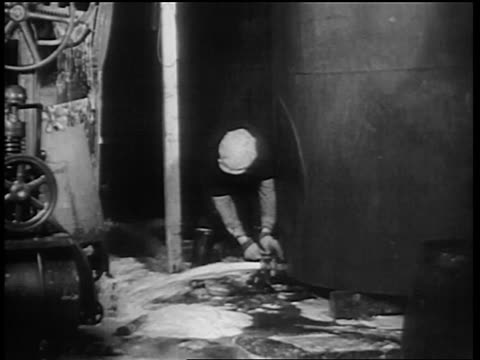 b/w 1932 man opening valve at bottom of large vat / beer spraying out onto floor / chicago - anno 1932 video stock e b–roll