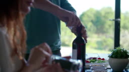 Man opening wine bottle.Four caucasian friends people mediterranean italian salad,meat steak and bread lunch or dinner. Summer party at home in modern house 4k handheld video