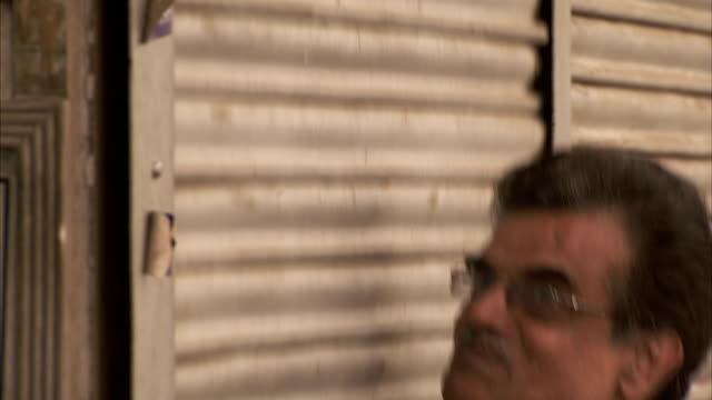 a man opens a shop shutter. - shutter stock videos & royalty-free footage