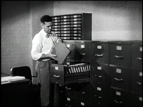 man opens filing cabinet and pulls out accounting books flips through them man opens filing cabinet inspects files on december 31 1948 - filing cabinet stock videos & royalty-free footage