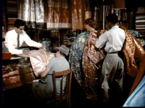 1957 montage man opens security gate on shop front/other man winds turban on head/interior shop indian silks + saris, chinese brocades, mandarin jackets, fine embroideries, jade statues + carved ivory, dolls, knick knacks / singapore / audio - display cabinet stock videos & royalty-free footage