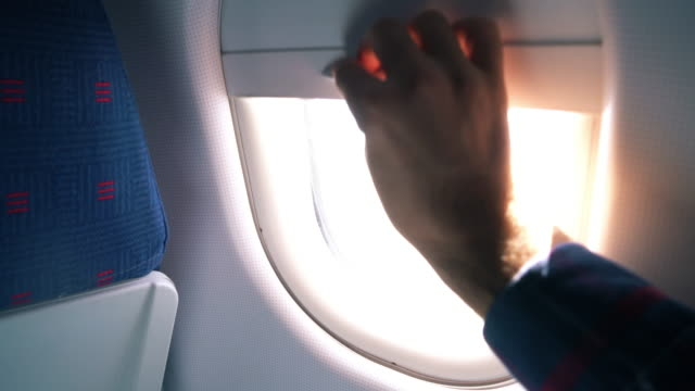 pov close up: man opens the airplane window and lets blinding light into cabin - blinds stock videos & royalty-free footage