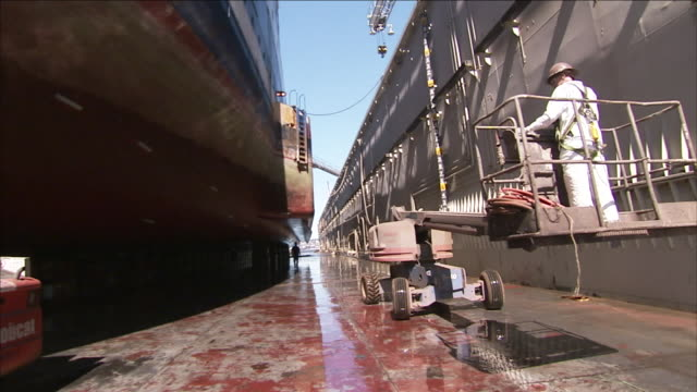 a man operates a cherry picker in between two ships. - cherry picker stock videos & royalty-free footage