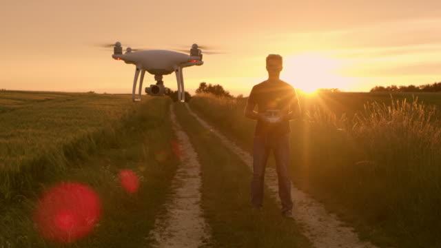 vídeos y material grabado en eventos de stock de hombre de ws un drone de funcionamiento al atardecer - operar