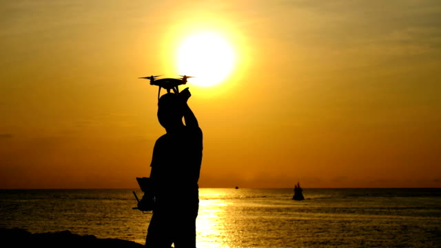 Man operating a drone taking off on the beach at sunrise