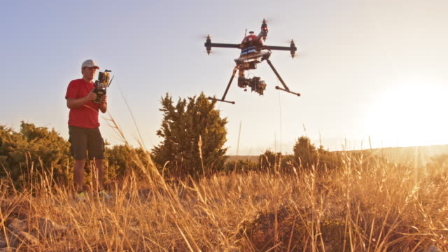 DS Man operating a drone taking off the hill and into the sunset