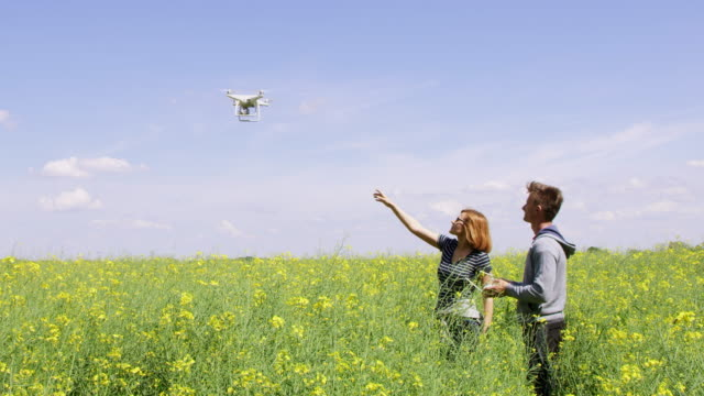 WS Man operating a drone to land in woman's hand