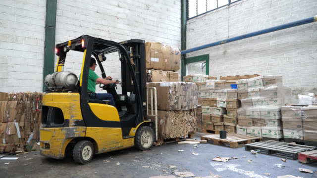 Man operating a forklift truck at a recycling factory moving a stack of cardboard boxes