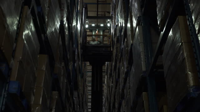 Man operating and descending forklift machinery in darkened aisle of warehouse