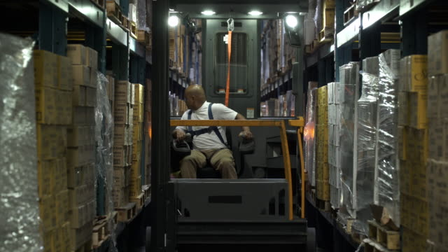 man operating and reversing machinery in warehouse aisle by stock - rückwärts fahren stock-videos und b-roll-filmmaterial