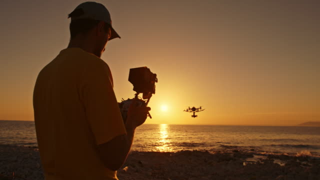 Man operating drone from beach at sunset