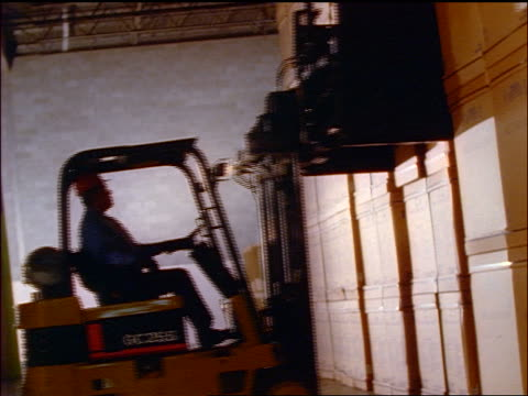 vídeos de stock, filmes e b-roll de canted man operating forklift in warehouse taking box from stack + moving past camera - moving past