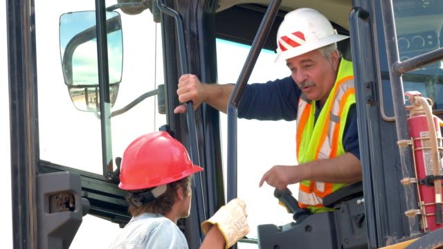 man operating large loader talking with worker - roadworks stock videos & royalty-free footage