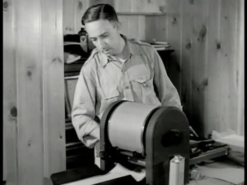 stockvideo's en b-roll-footage met man operating mimeograph duplicating machine cu machine printing out paper copies into stack arlington virginia - kopiëren