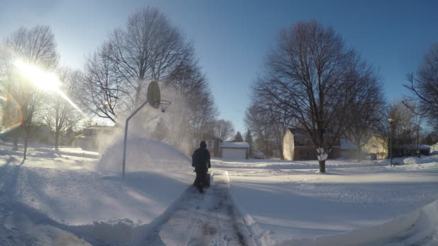 Man Operating snow blower moving away from camera