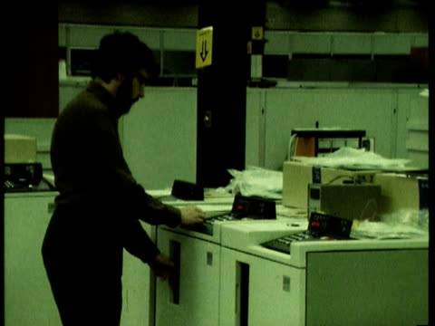 man operating tektronix 465 oscilloscope computer in income tax office. people working on computers in the 1980s on august 08, 1980 - オシロスコープ点の映像素材/bロール