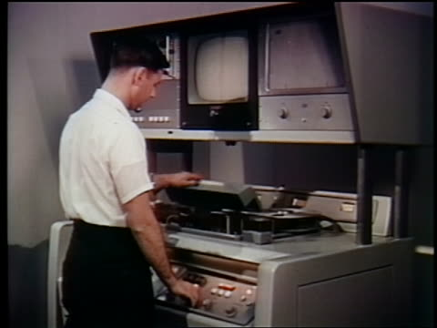 vídeos de stock e filmes b-roll de man operating video tape machine / first satellite broadcast / documentary - videogravador
