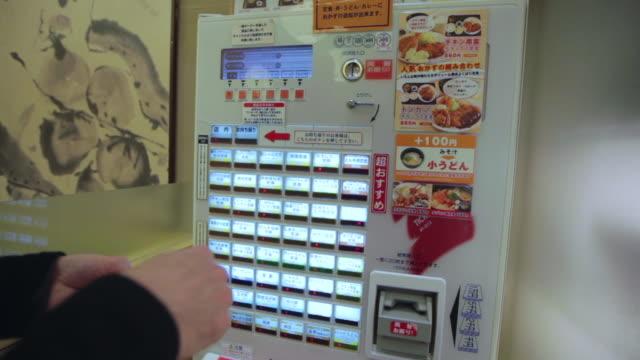 man ordering food on an automatic machine in a restaurant in kyoto - 注文する点の映像素材/bロール