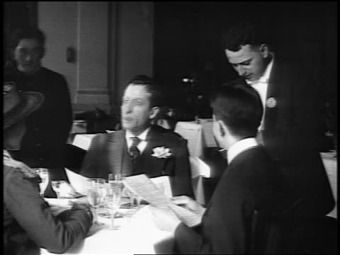 B/W 1916 man ordering for group at table in posh restaurant as waiters pour them drinks / news.