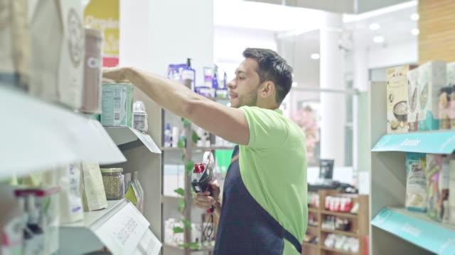 mann organisiert das supermarktregal - lateinische schrift stock-videos und b-roll-filmmaterial