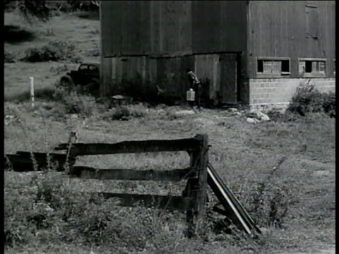 man out of backside of barn w/ containers. int vs 'boss' showing undercover treasury agent around, introducing to workers. vs agent & 'boss' looking... - 放浪者点の映像素材/bロール