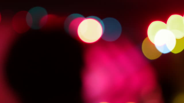 A man, out of focus, at a music festival enjoying the sound and the brilliantly colourful lights