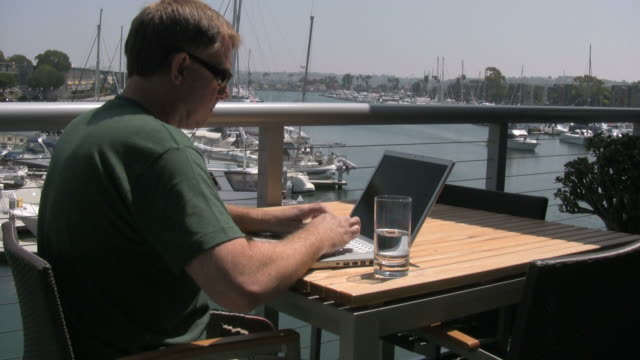 (HD1080i) Man Outside Working on Laptop, Waves to Passing Boat