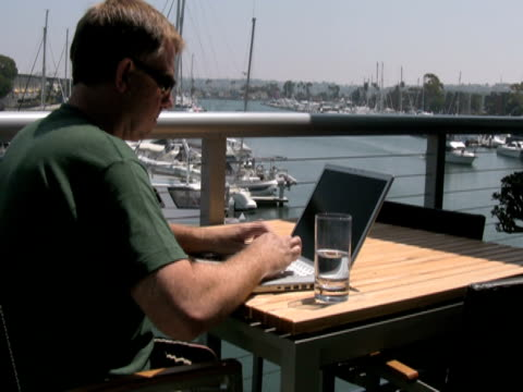 man outside working on laptop, waves to passing boat - only mature men stock videos & royalty-free footage