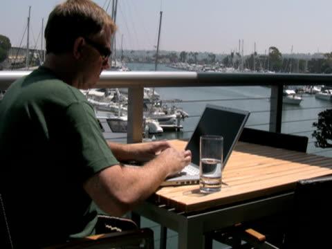 mann mit laptop im freien arbeiten, wellen zu übergeben boot - only mature men stock-videos und b-roll-filmmaterial