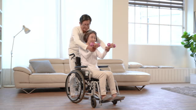 man over 60 helping woman over 60 who exercise in a wheelchair - ハンドウェイト点の映像素材/bロール