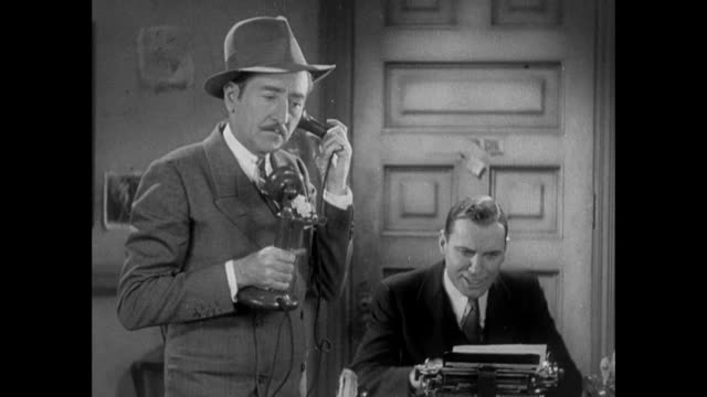 1931 man (adolph menjou) paces as reporter (pat o'brien) rips paper put of typewriter and starts over - 1931 stock videos & royalty-free footage