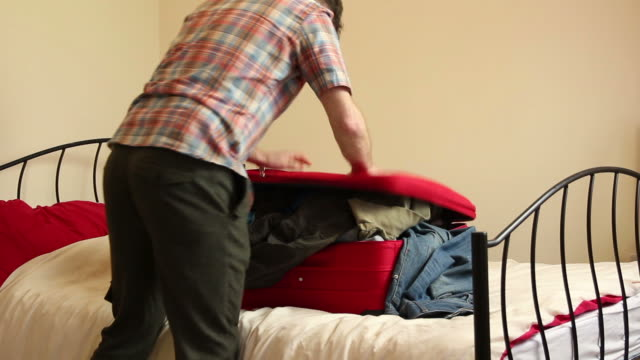 Man packing his suitcase - Hard to close!