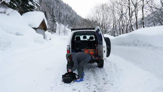 mann taschen packen und laden fahrzeug auf verschneiten straße - eskapismus stock-videos und b-roll-filmmaterial