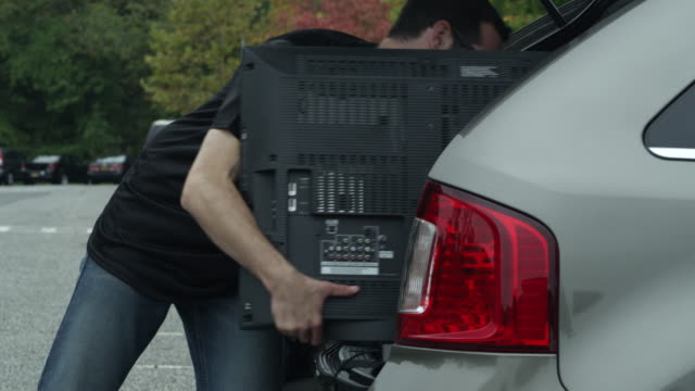 man packing up his car after tailgating - kühlbehälter stock-videos und b-roll-filmmaterial