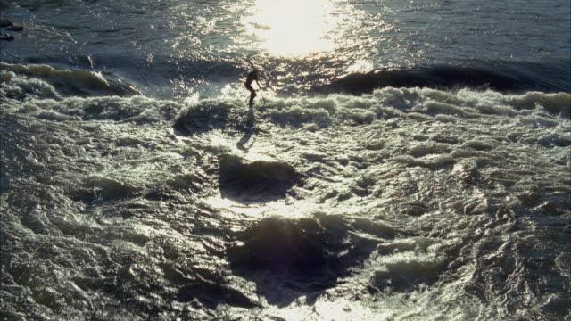 slo mo ws ha man paddle-boarding through waves in river / aspen, colorado, usa - balance stock videos & royalty-free footage