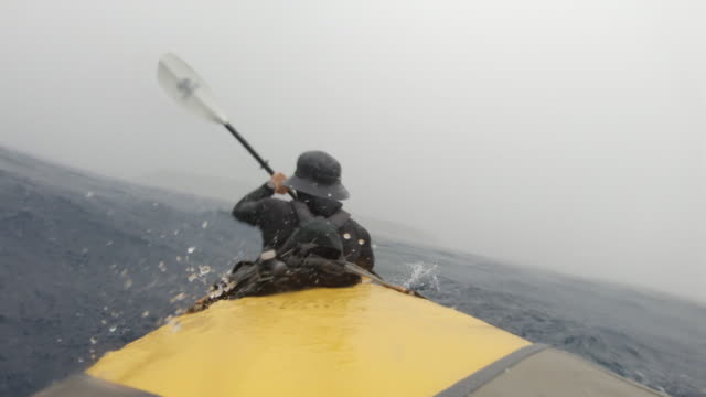 WS A man paddles a kayak through a storm