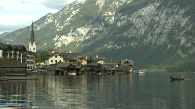 man paddles boat across hallstattersee towards lakeside buildings and church with mountains in background, hallstatt - アッパーオーストリア点の映像素材/bロール