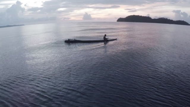 vídeos y material grabado en eventos de stock de man paddles boat off coast of indonesia, wide - ancho