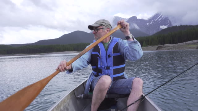 man paddles boat while dangling fishing line into mountain lake - using a paddle stock videos & royalty-free footage