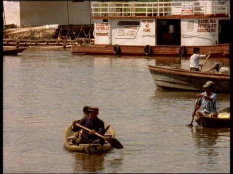 man paddles canoe with passenger on board among other water taxis belen peru - 水上タクシー点の映像素材/bロール