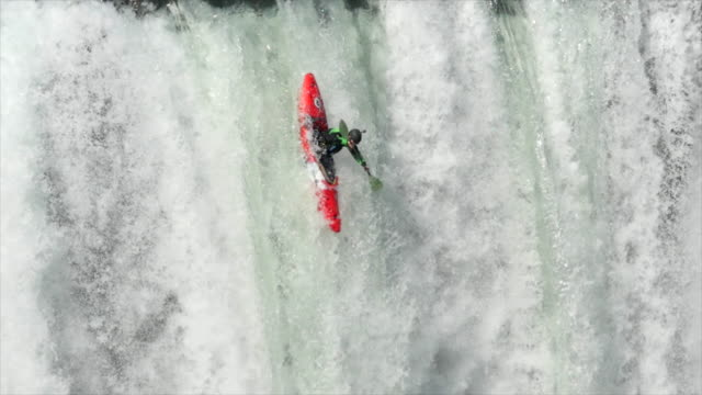 a man paddles his kayak down a waterfall on river rapids. - rapid stock videos & royalty-free footage