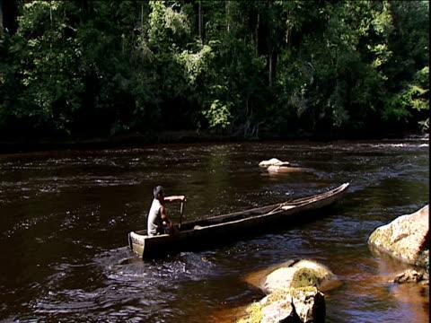 Man paddles wooden canoe against strong current of river Amazon Rainforest Venezuela