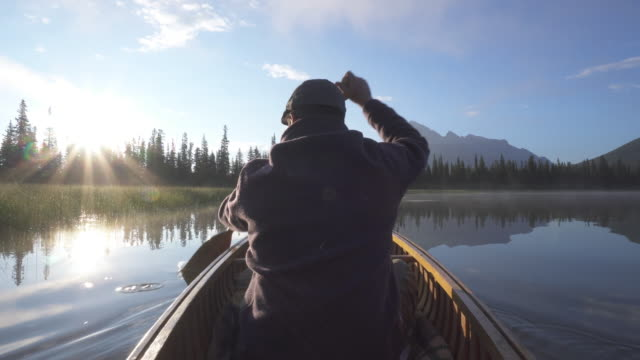 Man paddles wooden canoe into mountain lake